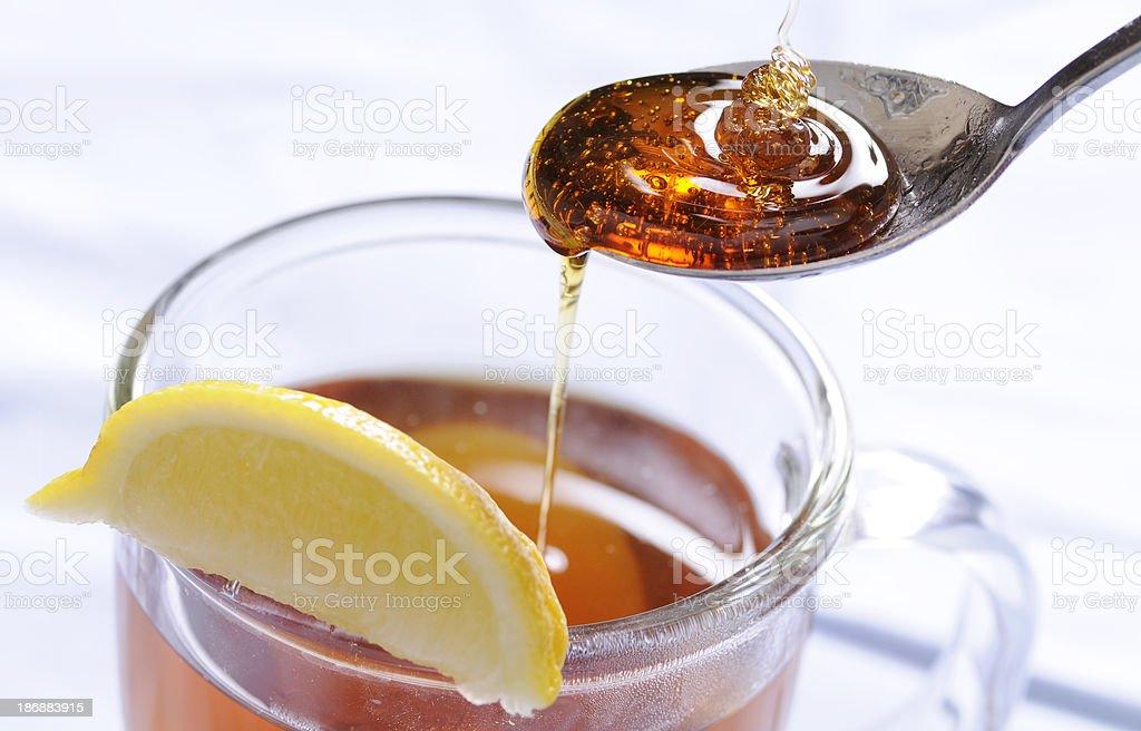 Honey Drizzle into Tea with Lemon stock photo