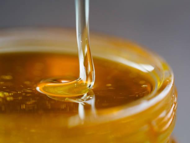 honey falling in jar extreme close up - mel imagens e fotografias de stock