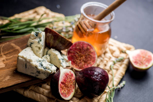 honey, figs and cheese on a wicker plate. Black background stock photo