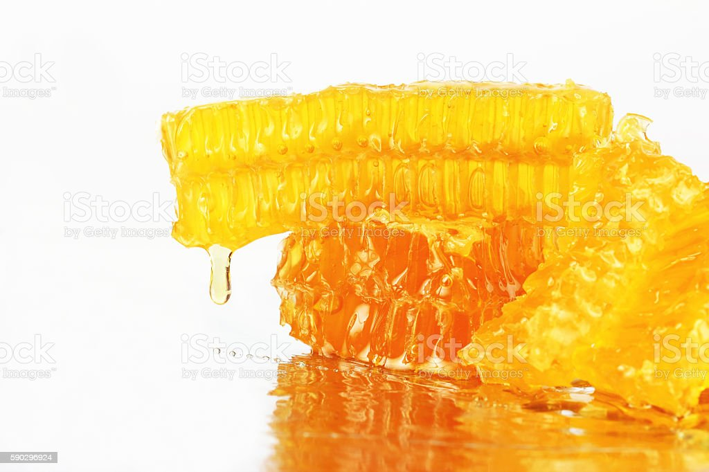 honey flowing from the honeycombs on a light background royaltyfri bildbanksbilder