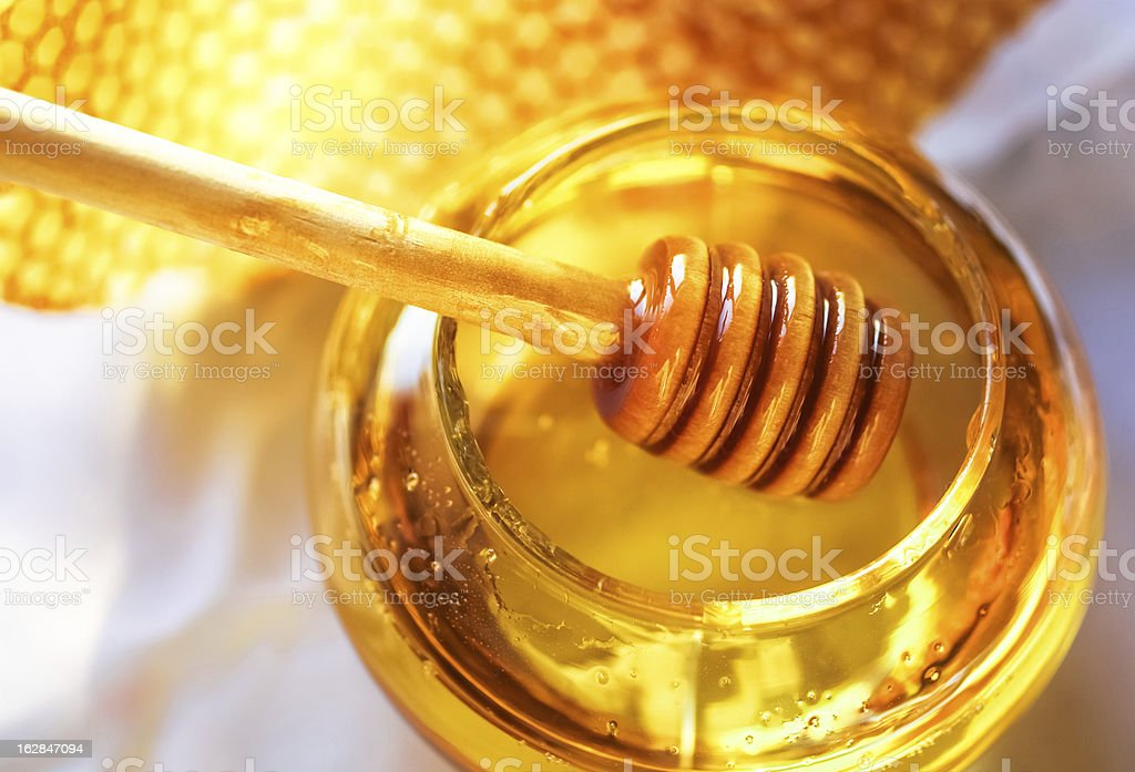 Honey in a glass jar next to honeycombs Honey dipper on the bee honeycomb background. Honey tidbit in glass jar and honeycombs wax. Apiculture Stock Photo