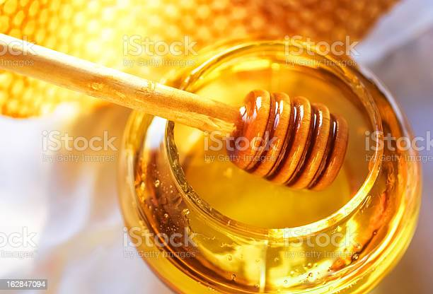 Honey In A Glass Jar Next To Honeycombs Stock Photo - Download Image Now