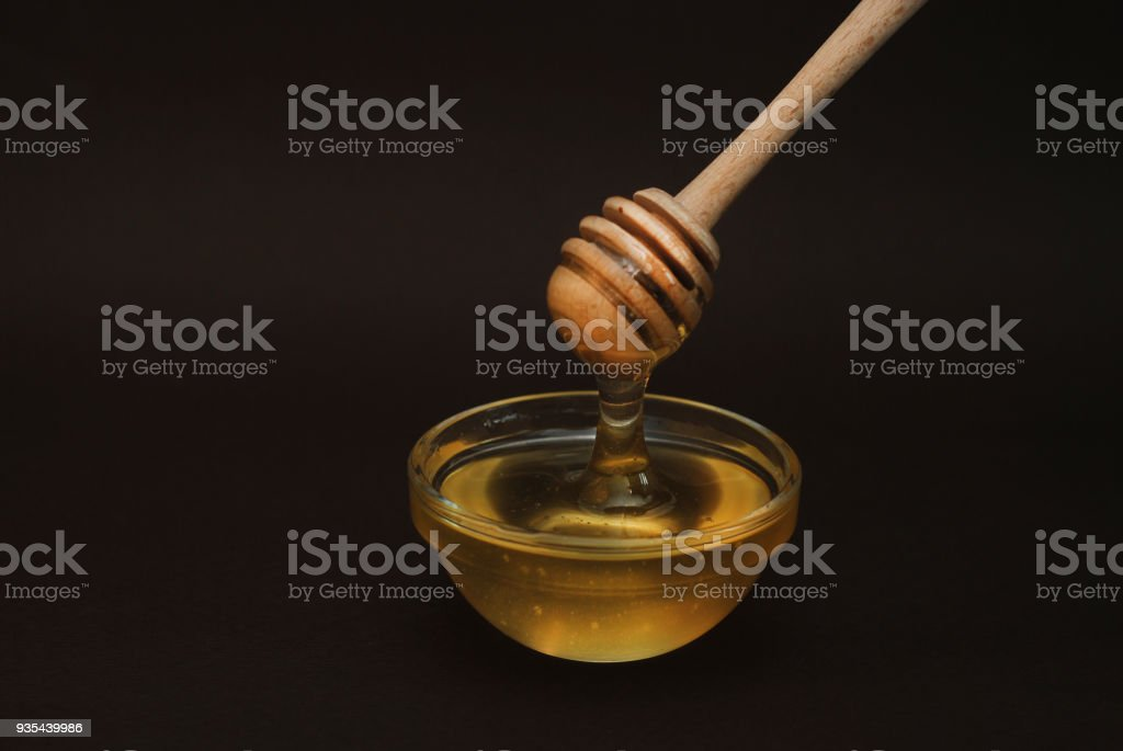 Honey in Glass bowl with dipper over dark Background Isolated with copy space. stock photo