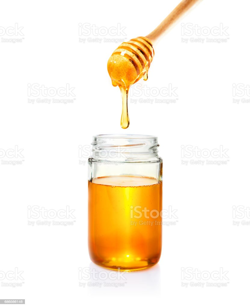 honey in glass jar and dripping from wooden dipper, on isolated white background royalty-free stock photo