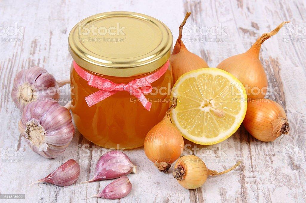 Honey in glass jar, onion, lemon and garlic, healthy nutrition stock photo