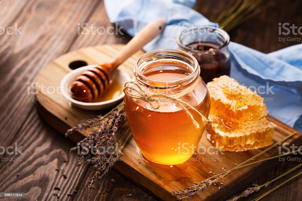 Honey in jar and bunch of dry lavender stock photo