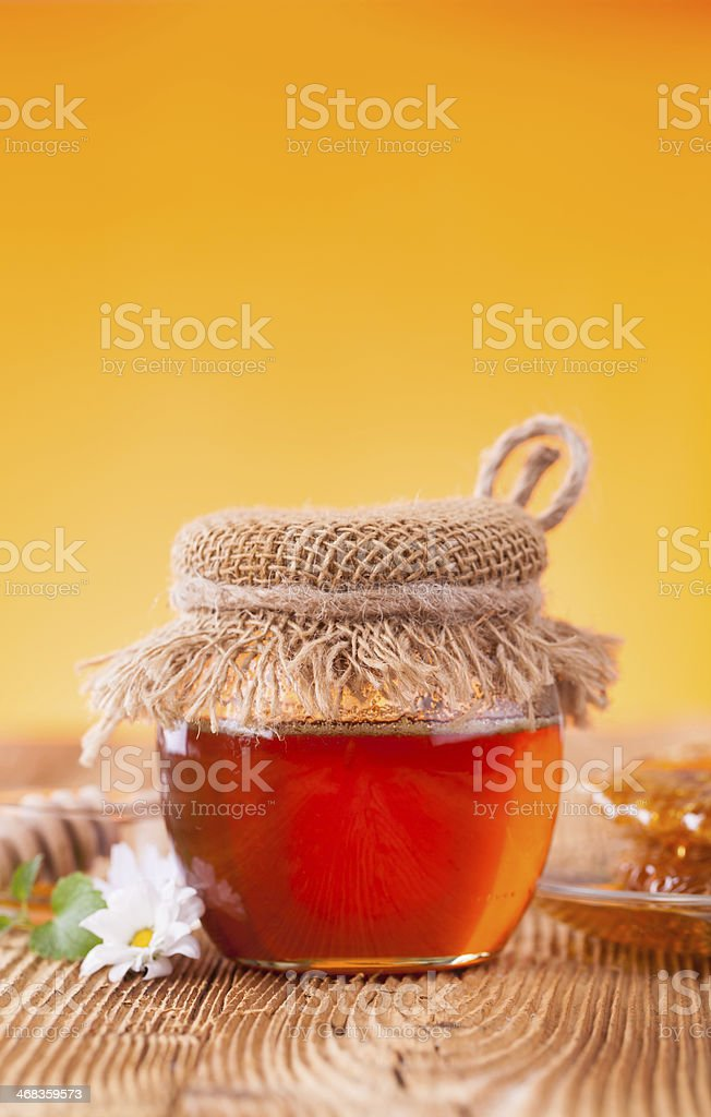 Honey in jar with honeycomb and wooden drizzler royalty-free stock photo