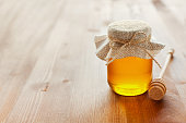 Natural honey in a pot or jar with twine tied in a bow and honey dipper on a wooden background