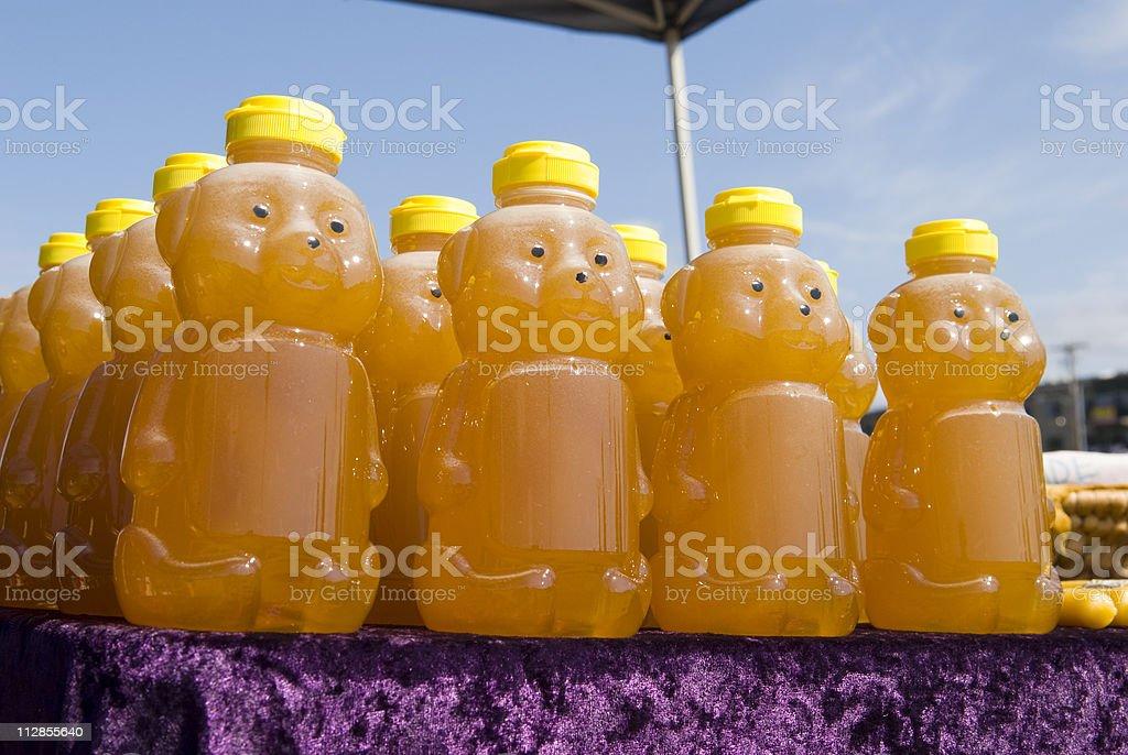 Honey in plastic bear-shaped bottles at farmer's market foto