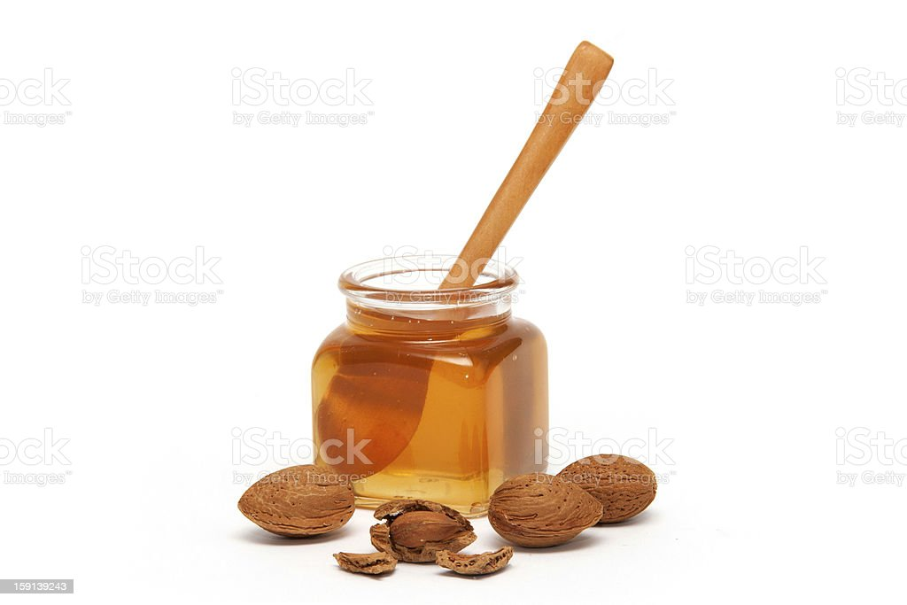 Honey in the jar and almonds stock photo