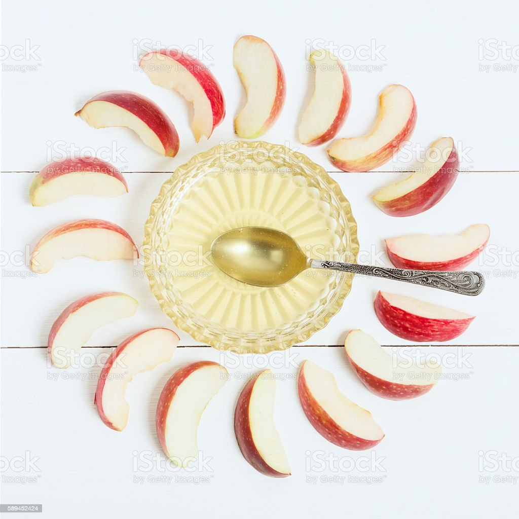 Honey in the vase, spoon and apples around on wooden stock photo