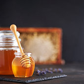 istock Honey jar, honeycomb and wooden spoon in jar on black background. Copy space. Autumn harvest concept. 1176624246