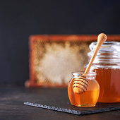 istock Honey jar, honeycomb and wooden spoon in jar on black background. Copy space. Autumn harvest concept. 1176630316