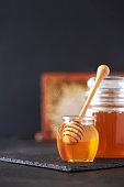 istock Honey jar, honeycomb and wooden spoon in jar on black background. Copy space. Autumn harvest concept. 1176630326