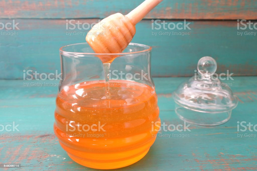 Honey jar on a wooden turquoise background stock photo