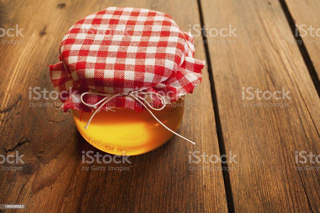 Honey jar on picnic table royalty-free stock photo