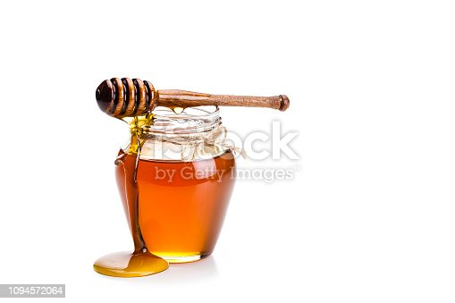 Open honey jar with a honey dipper dripping honey on the jar and table. The composition is isolated on white background at the left of an horizontal frame leaving useful copy space for text and/or logo. High key DSRL studio photo taken with Canon EOS 5D Mk II and Canon EF 70-200mm f/2.8L IS II USM Telephoto Zoom Lens