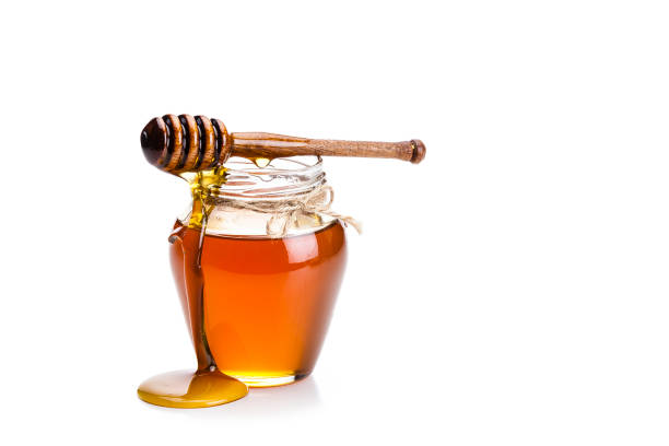 Honey jar with honey dipper isolated on white background Open honey jar with a honey dipper dripping honey on the jar and table. The composition is isolated on white background at the left of an horizontal frame leaving useful copy space for text and/or logo. High key DSRL studio photo taken with Canon EOS 5D Mk II and Canon EF 70-200mm f/2.8L IS II USM Telephoto Zoom Lens honey stock pictures, royalty-free photos & images