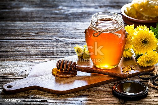 Apiculture industry concepts. Organic honey in a glass jar shot on rustic wooden table. The honey jar is on a small wooden cutting board and in front of it is a honey dipper with flowing honey. Yellow flowers are at the right and complete the composition. Useful copy space available for text and/or logo. Predominant colors are yellow and brown. Low key DSRL studio photo taken with Canon EOS 5D Mk II and Canon EF 100mm f/2.8L Macro IS USM.
