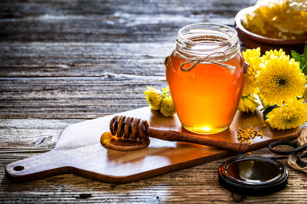 honey jar with honey dipper shot on rustic wooden table - miele foto e immagini stock