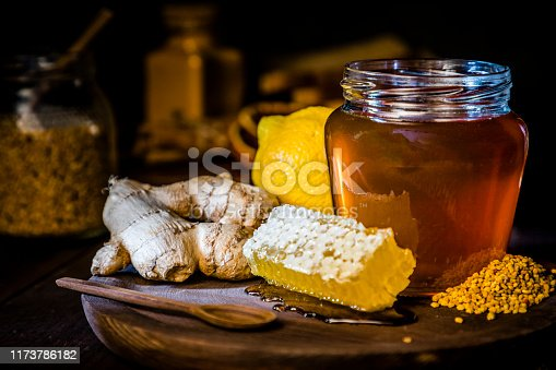 Front view of a honey jar surrounded by lemon, ginger, a honeycomb, a honey dipper and bee pollen. Objects are on a rustic cutting board and against black background. Low key DSLR photo taken with Canon EOS 6D Mark II and Canon EF 24-105 mm f/4L