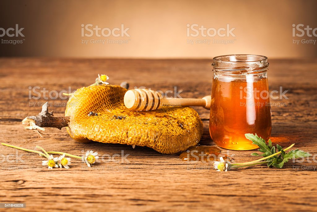 honey jar with honeycomb on wooden table stock photo