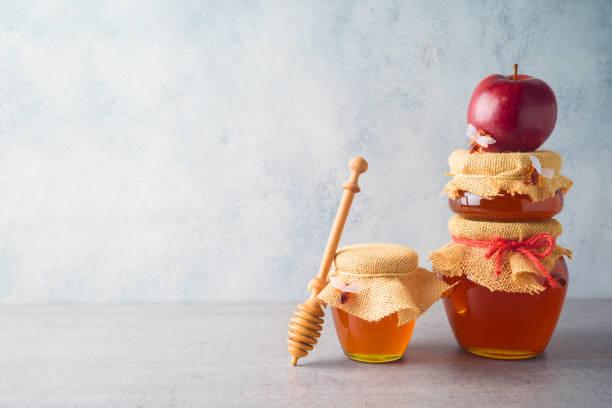 Honey jars and apple over grey background stock photo