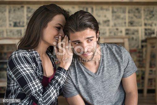 Happy woman whispering a secret to her boyfriend.