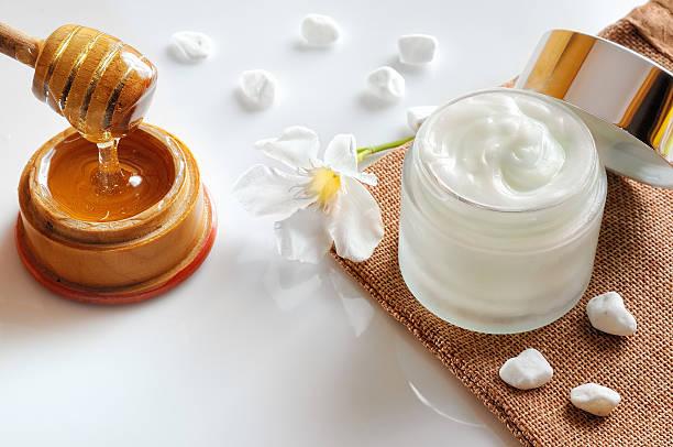 Miel crema hidratante con piedras y flor de vista superior - foto de stock