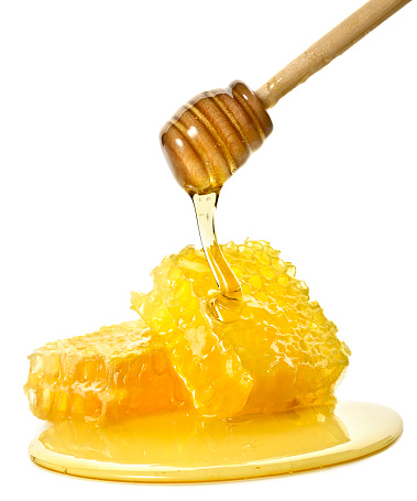 Fresh honey flowing from a dipper on two slices of honeycomb.  Isolated on a white background.