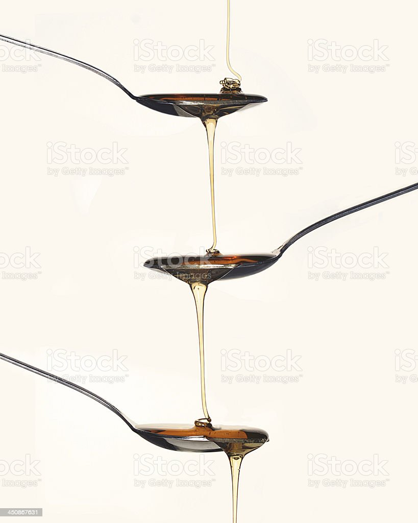 Honey Poured From one Spoon To The Next royalty-free stock photo