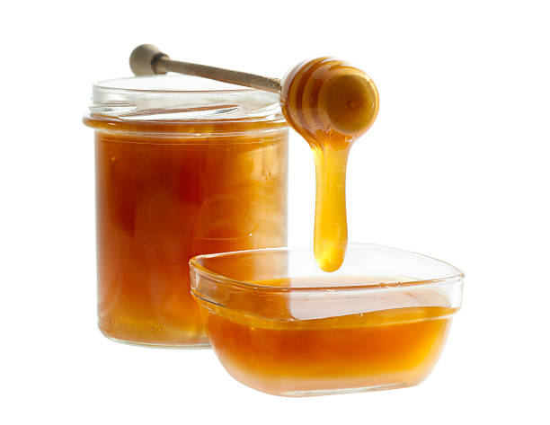 Honey Pouring From dripper Into The Bowl stock photo