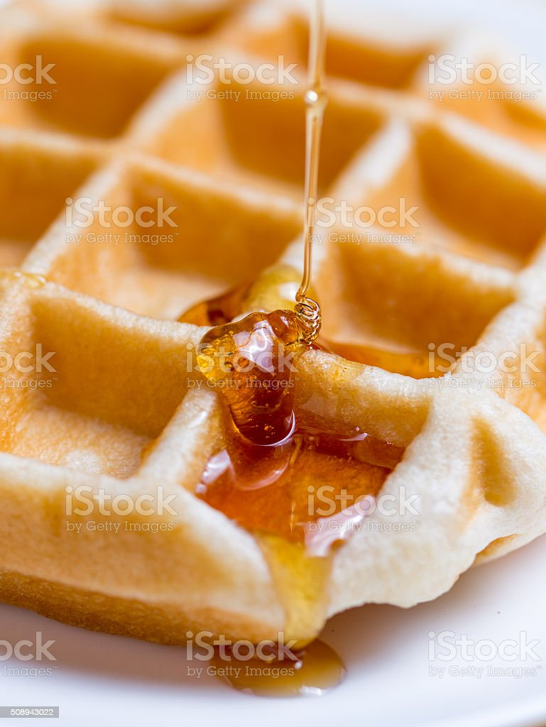 Honey pouring on a fresh waffles stock photo