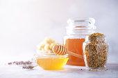 istock Honey products background. Honeycomb frame, bee pollen granules, honey in glass pot on grey concrete background. Copy space. Autumn harvest concept. 1176629881