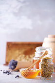 istock Honey products background. Honeycomb frame, bee pollen granules, honey in glass pot on grey concrete background. Copy space. Autumn harvest concept. 1176629910
