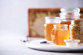 istock Honey products background. Honeycomb frame, bee pollen granules, honey in glass pot on grey concrete background. Copy space. Autumn harvest concept. 1176629937