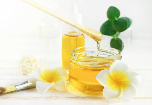 honig-spa-behandlung. goldenen honig jar, plumeria blumen gießen - wachsblume stock-fotos und bilder