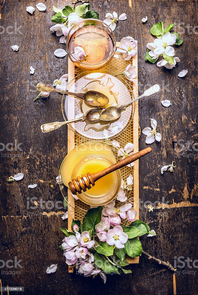Honey, tea and spring blossom on honeycomb stock photo
