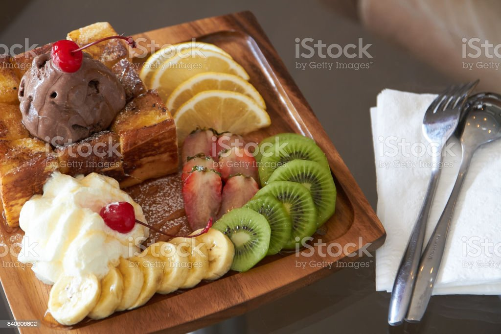 Honey Toast with strawberries, berries, kiwi, lemon, ice cream, whipped cream topped with caramel sauce on a wooden tray. stock photo