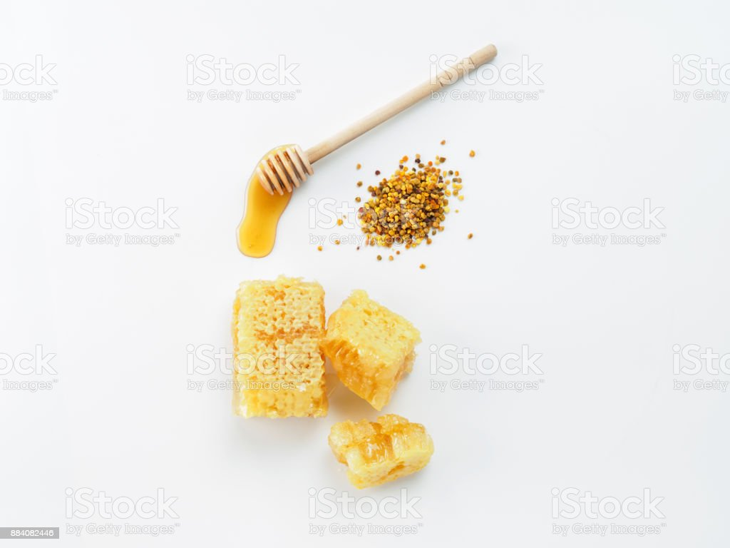 Honey with dipper, honeycomb and bee pollen on white background stock photo