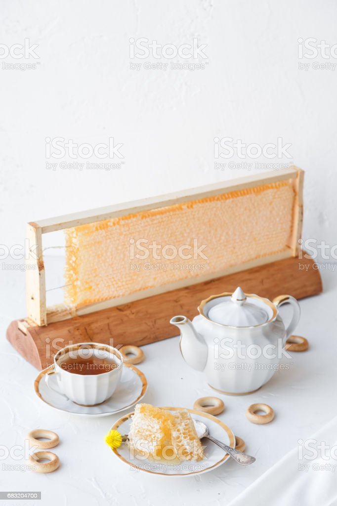 Honey with honeycomb and tea with teapot and flowers on the background, place for wording foto de stock royalty-free