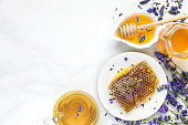 istock Honey with lavender tea and honeycombs with freash flowers on white marble table. healthy food. top view 1030580908