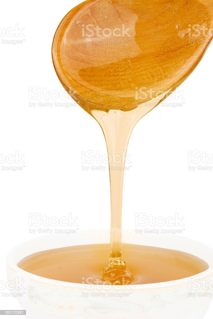 Honey with wood stick pouring royalty-free stock photo