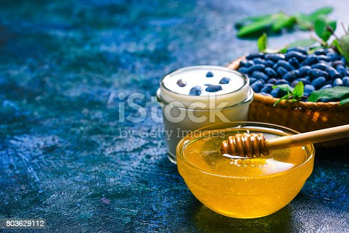 Glass bowl of honey, homemade yogurt and fresh honeysuckle berries in little basket  over spotty blue background. Close up