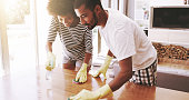 Shot of a cheerful young couple cleaning the surface of a table with cleaning equipment together at home