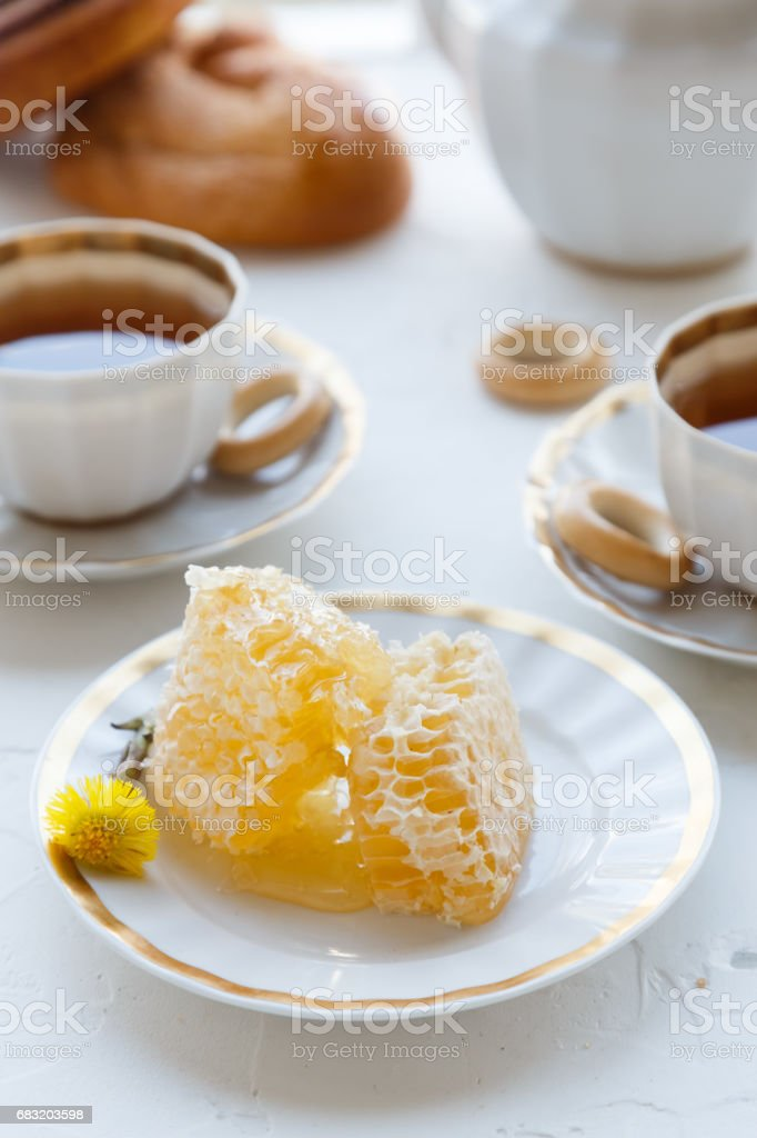 Honeycomb on a plate with tea cups on background royalty-free 스톡 사진