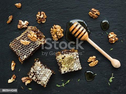 istock Honeycomb, walnuts and honey dipper on black slate tray over grunge dark backdrop 865944048