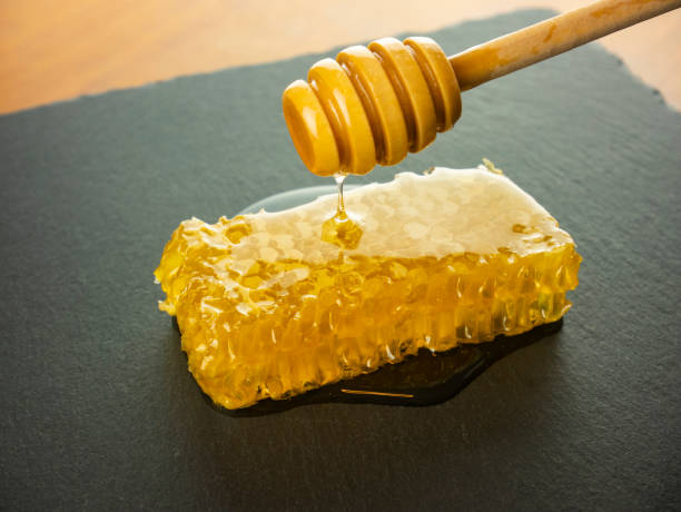 honeycomb with honey dipper on black slate plate stock photo