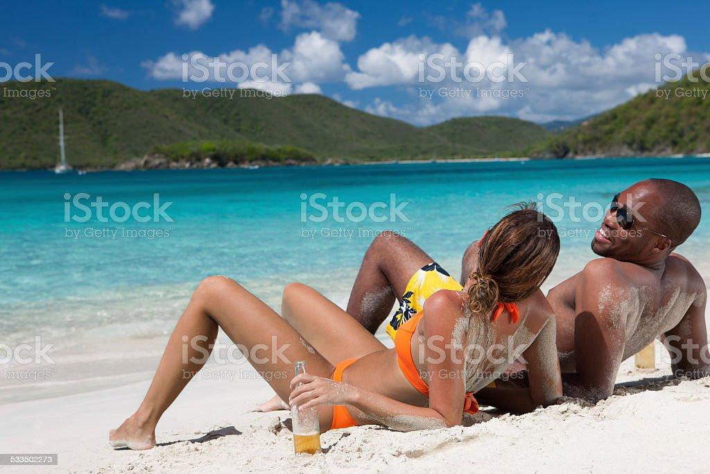 honeymoon couple drinking beers at a beach in St.John, USVI stock photo