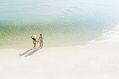 Honeymoon couple holding hand walking on beautiful white sand beach in summer - bird eye view